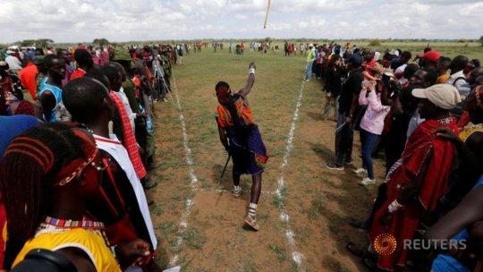 A Maasai warrior throws a traditional club.
