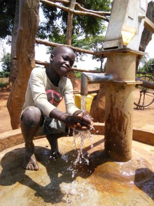 An excited resident of Angayiki B with clean water