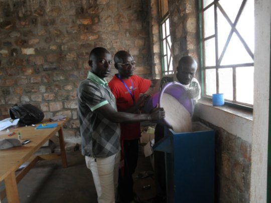 Educators adding sand to the water filter system