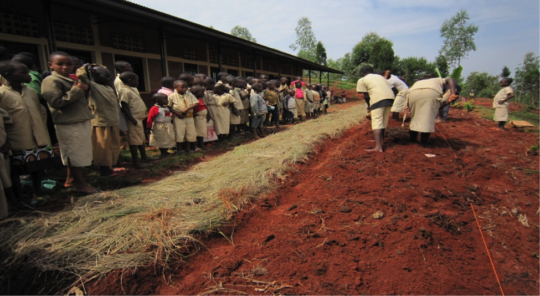 Youth adding manure to new garden at their school