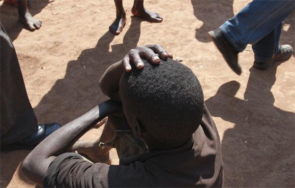 A boy with the head in his hands, Gitega Prison, Burundi