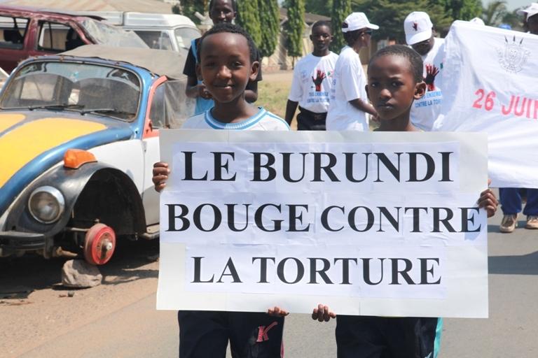 "Burundian kids hold a poster: ""Burundi moves forward again"""