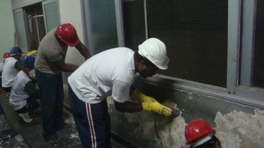 Masonry practical course. Scraping classroom walls