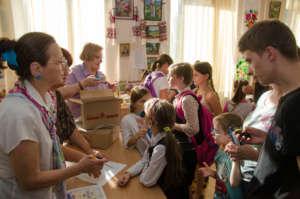 Distributing sets of school supplies to children