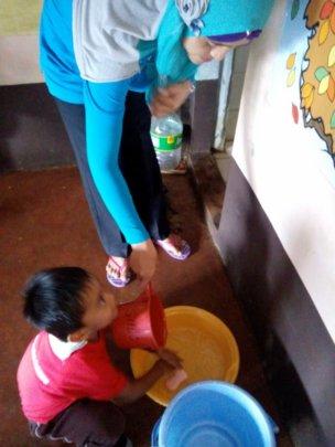 Kindergarten teacher assists student wash hands