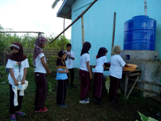 Students lining up to fill wash basins at Sahaya