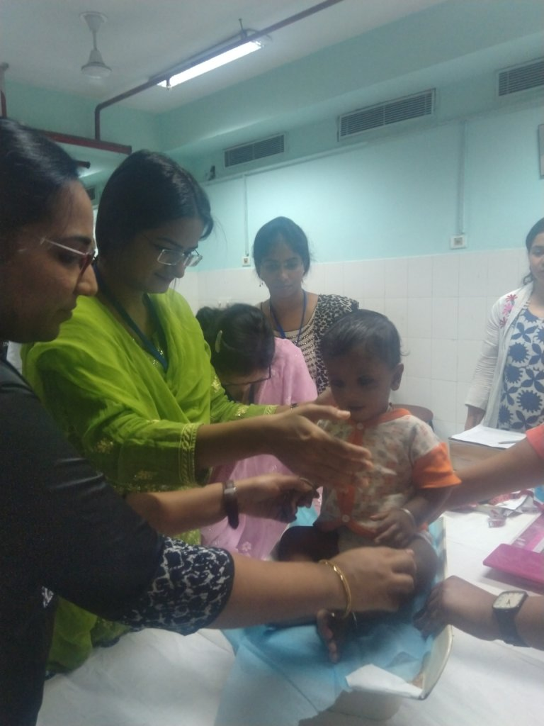 Participants weighing a child on weighing scale