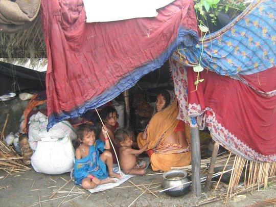 A family takes shelter under a tarpulin