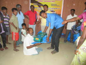 Disabled Person assisted with relief goods