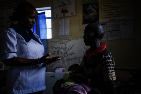 Nurse supporting child with malnutrition in Kenya