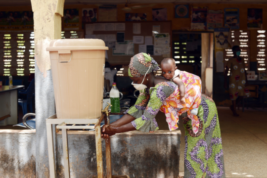 A mother using a hand-washing facility