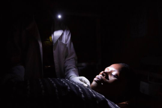 Midwife Holding Cell Phone At Night