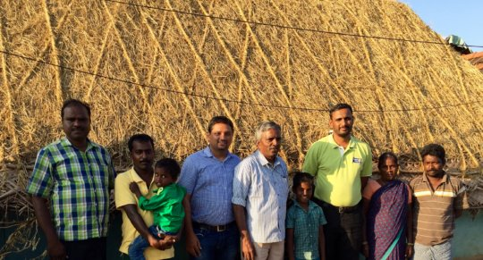 Our team and beneficiaries stand against new roof