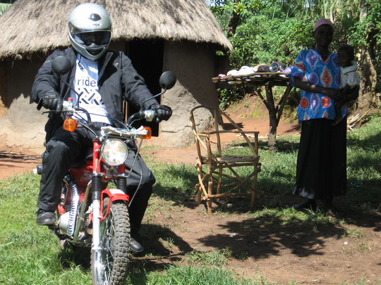 A carer from Vumilia on their motorcycle