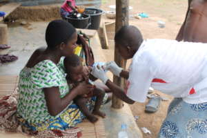 A Community Health Worker treats a child at home
