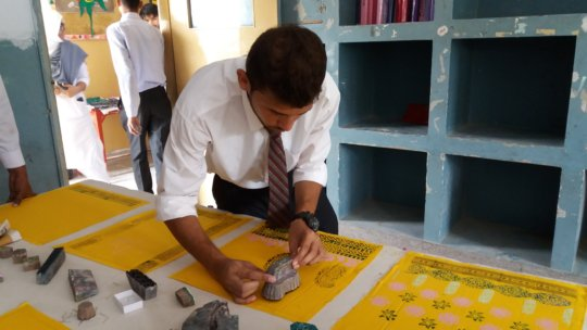 Trainee completing his block printing assignment