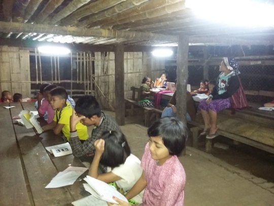 Students studying at night with solar lighting
