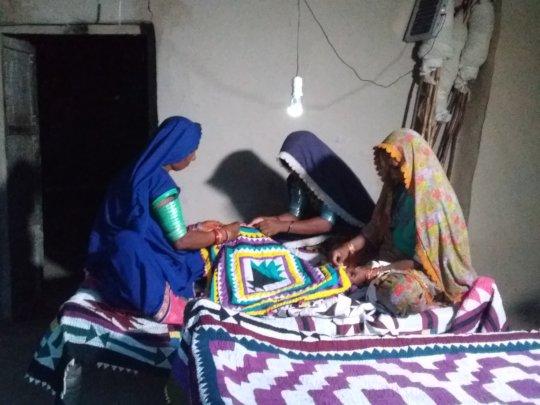 Women sewing relee work in night via solar bulb