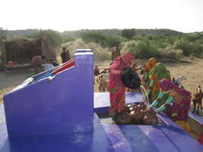 Women filling their water pitchers.