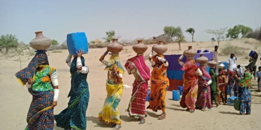 Women with pitchers of sweet drinking water.