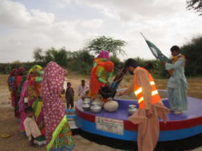 Women in their traditional attire filling water.