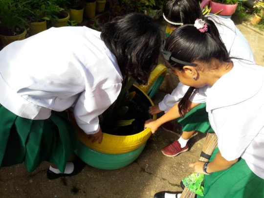 Little nurses empty stagnant water in playground