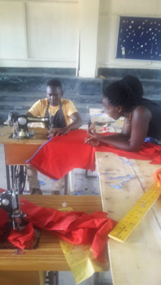 Clayan with his teacher  making an Apron
