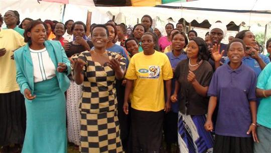 Olive Wolimbwa, WMI Manager,leads the borrowers in song