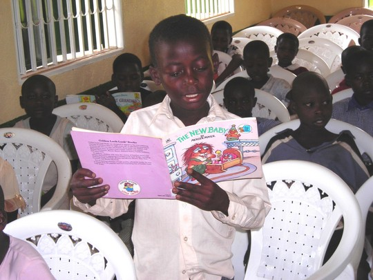 Buyohildren reading from the donated books in the new building.