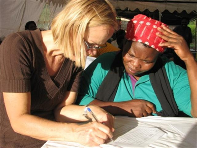 WMI Board Member, Trix Vandervossen, helps fill out loan forms