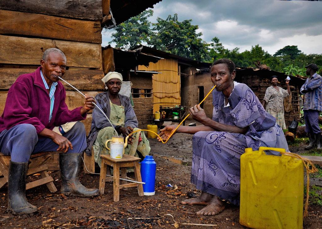 Members of Bulambuli village gather around to drink a borrower