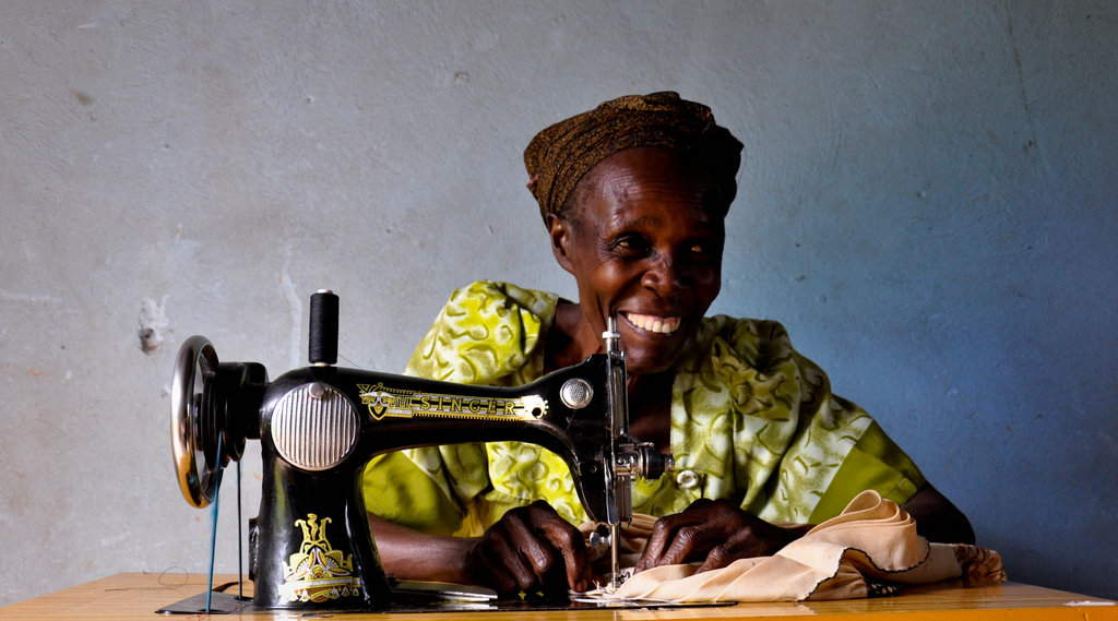 Jackline Nagudi smiles for the camera as she works at her sewing business. WMI