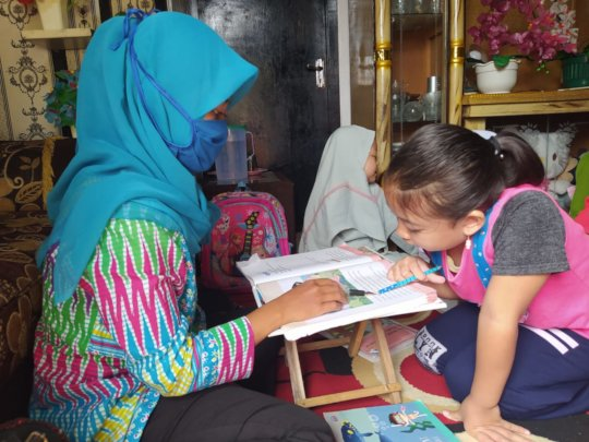 Mrs. Fatonah with her student at reading session