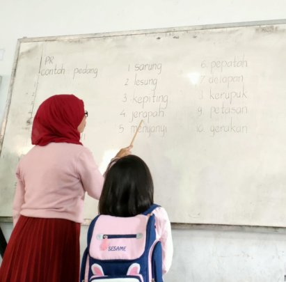 Mrs. Iin with her student on reading session