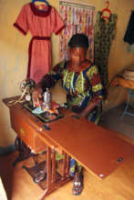 A project beneficiary in her tailoring shop