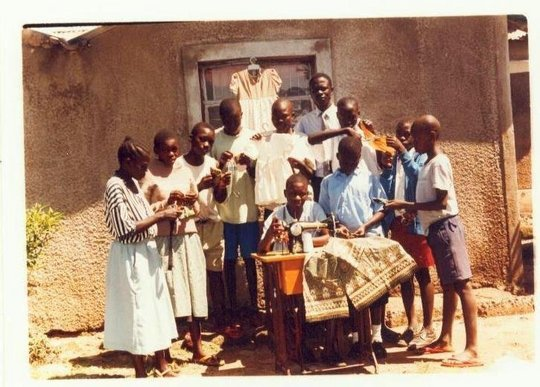 A group of children learning tailoring .