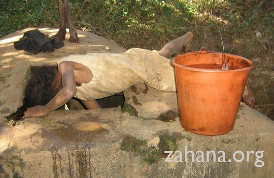 Girl gets water at Fiarenana's communal well