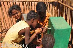 Children drinking from the communal water faucet