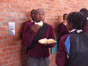Mfundo enjoying a sandwiche provided by donor funds
