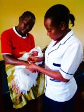 Midwife Brigid with new baby and mother