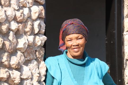 Lys standing in the doorway of her healing hut