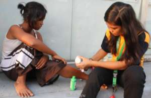 A junior health worker treats wounds of street kid