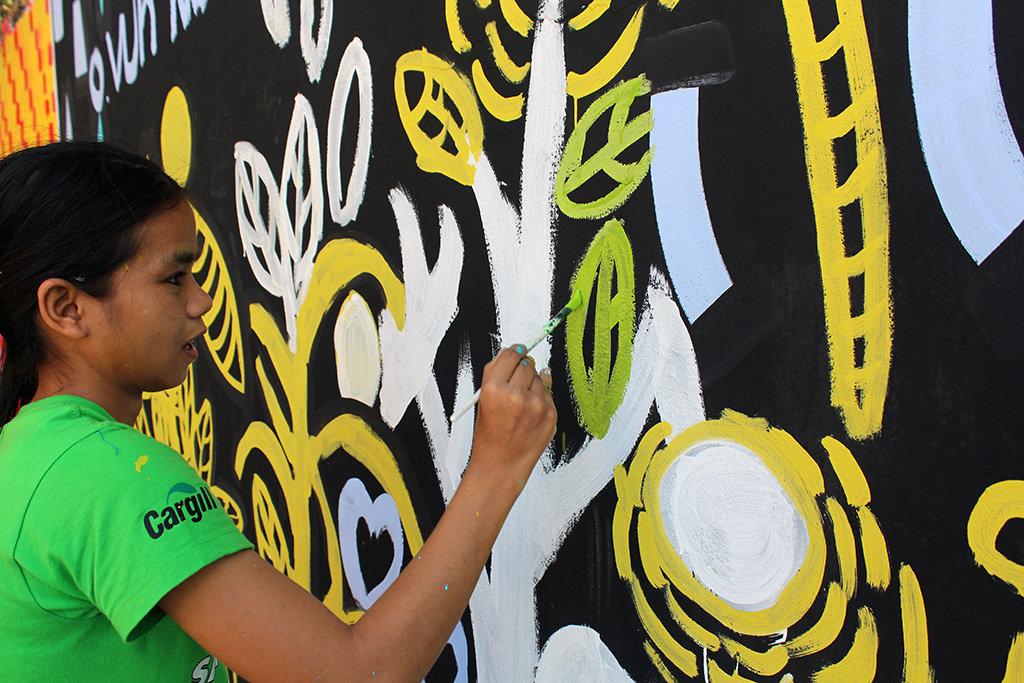 Savun painting a mural she designed