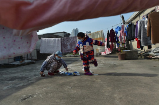 Children play games on the roof of shabby hostels.