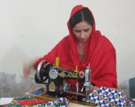 A girl using a sewing machine to stitch a dress