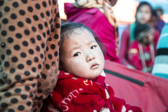 A baby rests while her mother attends awareness