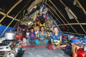 Three generations of women sit inside their home.
