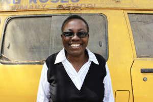 Aurelia in front of one of her school buses
