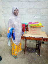 Aisha I., with her tailoring equipment & material