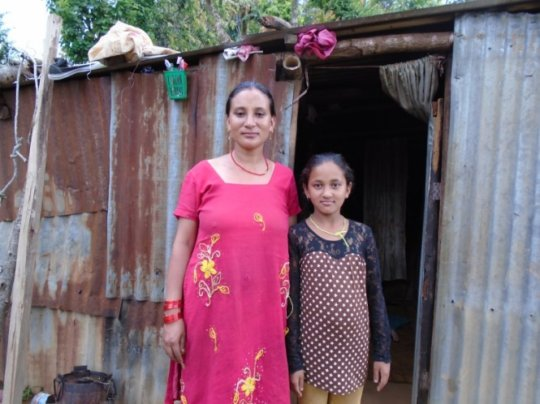 Samiksha with her mother in front of their home